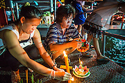 28 NOVEMBER 2012 - BANGKOK, THAILAND:  Women light the candles on their krathongs before placing them in the Chao Phraya River on Loy Krathong at Wat Yannawa in Bangkok. Loy Krathong takes place on the evening of the full moon of the 12th month in the traditional Thai lunar calendar. In the western calendar this usually falls in November. Loy means 'to float', while krathong refers to the usually lotus-shaped container which floats on the water. Traditional krathongs are made of the layers of the trunk of a banana tree or a spider lily plant. Now, many people use krathongs of baked bread which disintegrate in the water and feed the fish. A krathong is decorated with elaborately folded banana leaves, incense sticks, and a candle. A small coin is sometimes included as an offering to the river spirits. On the night of the full moon, Thais launch their krathong on a river, canal or a pond, making a wish as they do so.   PHOTO BY JACK KURTZ