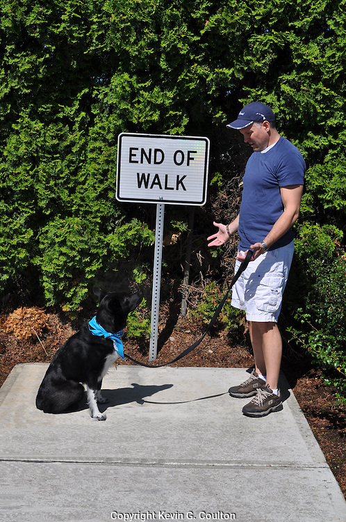 """Humorous photograph of a man with a dog on a leash in front of an END OF WALK sign with the dog wanting to walk more but the man indicating it is the """"end of the walk""""."""