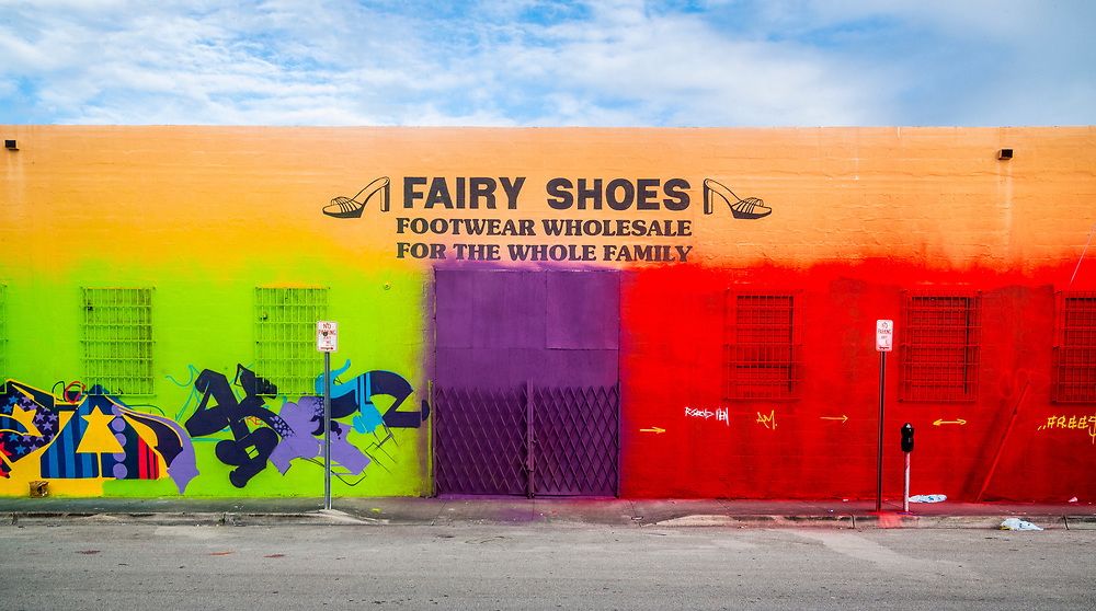 A Miami shoe warehouse with folk art paintings of footwear, plus vivid, spray painted colors and graffiti, also folk art.