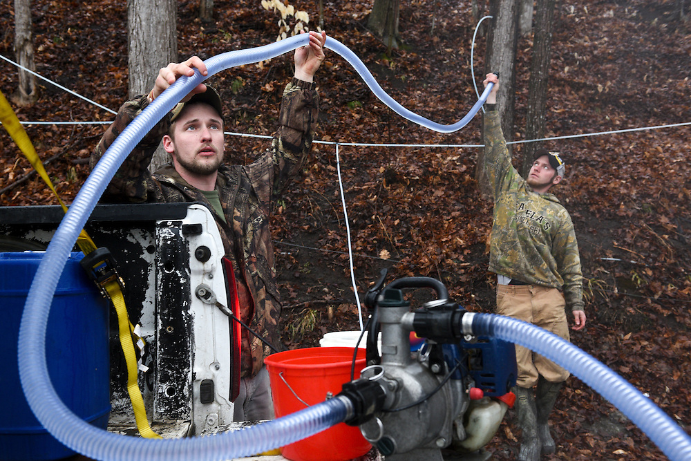 A.J. Potwin, of Sharon, left, and Scooter Cadwell, of Sharon, right, attempt to prime an uncooperative pump while collecting maple sap from about 150 taps for L.L. Potwin Services at their sugar bush in Quechee, Vt. Thursday, March 26, 2015. L.L Potwin also has about 1100 taps at a sugarbush in Sharon. (Valley News - James M. Patterson)<br /> Copyright © Valley News. May not be reprinted or used online without permission. Send requests to permission@vnews.com.
