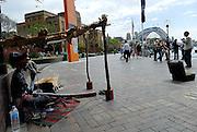 Male aboriginal busker, playing didjeridoo. Circular Quay, Sydney, Australia