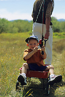 A young boy pretends to fish from the back of his red wagon in Jackson Hole, Wyoming.
