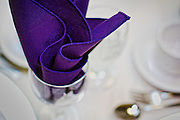 A purple linen serviette rests in a wine glass as part of a table setting.