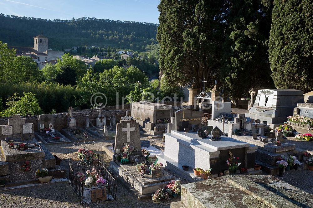 The village cemetery of Lagrasse and the church of Sant-Michel in the distance, on 21st May 2017, in Lagrasse, Languedoc-Rousillon, south of France. Lagrasse is listed as one of Frances most beautiful villages and lies on the famous Route 20 wine route in the Basses-Corbieres region dating to the 13th century.