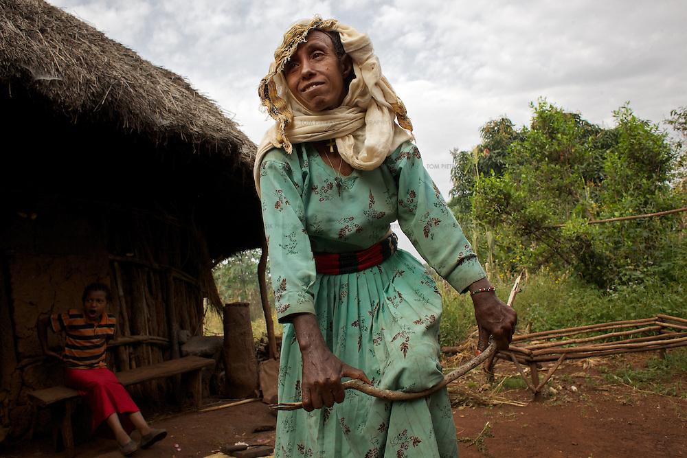 Belaynesh prepares firewood while cooking breakfast for her neice (looking on) and herself outside their home in the village of Amba Zetegn. <br /> <br /> Belaynesh Hussen (age 50) lives with her niece Tsehaynesh Bistegn, age 10, in a thatched house in Amba Zetegn, 20km from Assosa town. She farms sorghum, maize, teff and soya, all sold through the local farmers co-operative society of which she has been a part for the past three years. This village co-op is affiliated to the Assosa Farmers Multipurpose Cooperative Union.<br /> <br /> Growing oil seeds presents challenges for the famers of Assosa in western Ethiopia. Many of the most vulnerable are forced to sell to when they cannot be guaranteed a good price for their product. Farms are often located in isolated areas which entails huge amounts of time and effort simply getting seeds to market. Many farmers do not have the resources to properly invest in their land and are tied into exploitative loan arrangements with brokers that deny them the chance to take proper control of their farms. And, as with other agricultural products, it is those agents that process the seeds into oil that secure the greatest profit, very little of which trickles down to benefit the farmer.<br /> <br /> In response to these pressures, twenty farming cooperatives have formed the Assosa Farmers Multipurpose Cooperative Union. By working together, individual farmers are able to pool their resources and squeeze out exploitative agents and brokers. The Union has sufficient capital that it can afford to wait for prices to reach a level at which it is profitable to sell seeds to market. The Union provides loans to constituent members together with training and advice to help farmers make better use of their land. And by collectively hiring vehicles through the Union, farmers need not spend so much time ferrying their produce to market. <br /> <br /> All these measures benefit farmers and have now provided the Assosa Farmers Multipurpose Coope