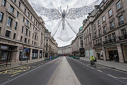 © Licensed to London News Pictures. 06/11/2020. LONDON, UK.  Christmas decorations overhead in a quiet Regent Street on day 2 of the second day of lockdown in England imposed by the UK government.  Restrictions are expected to last until 2 December in an attempt to control the spread of the ongoing coronavirus pandemic.  Photo credit: Stephen Chung/LNP