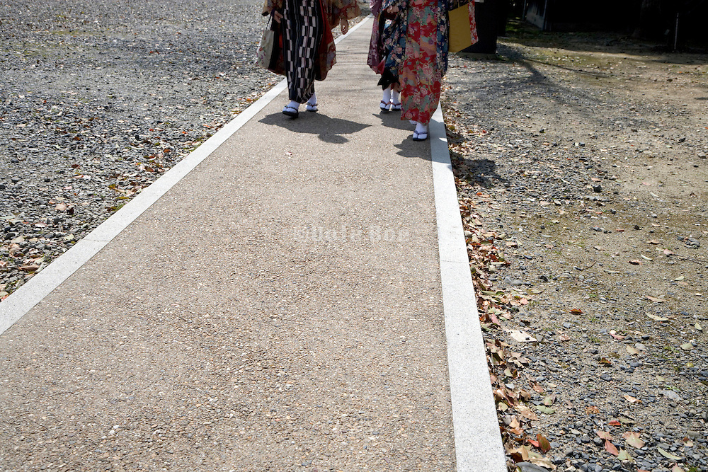 3 girls walking on a path in traditional Japanese clothing