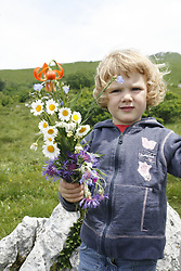 Child with flowers. (Photo by Vid Ponikvar / Sportida)