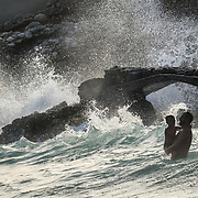 Father and son in the tumultuous waves of Nerja beach.