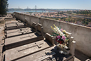Graves and fading flowers overlook the Ponte 25 de Abril<br /> bridge and the district of Alacantara in the western Portuguese capital, on 14th July 2016, at Prazeres Cemetery, Lisbon, Portugal. Prazeres Cemetery Cemitério dos Prazeres is the largest cemetery in Lisbon, Portugal, located in the west part of the city in the former Prazeres parish. It was created in 1833 after the outbreak of a cholera epidemic. Many famous Portuguese citizens are buried here, including artists, authors and government figures, and the cemetery features many large mausoleums built in the 19th century.