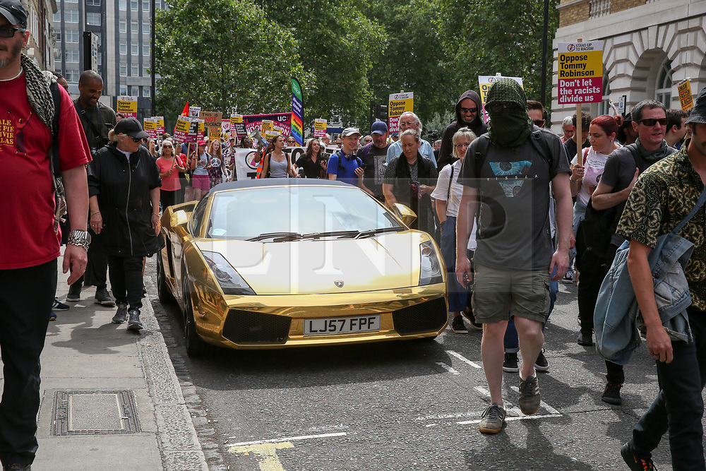 © Licensed to London News Pictures. 03/08/2019. London, UK. Anti Tommy Robinson protesters walk past a golden Lamborghini during a demonstration in central London. Last month Tommy Robinson was given a nine-month prison sentence at Old Bailey after he was found guilty of contempt of court.. Photo credit: Dinendra Haria/LNP