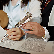 Bat Mitzvah girl's hand holds yad pointer on Torah scroll with her father's hand on top of her hand