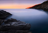 A view at dawn of Punta Cappel Rosso, the southern tip of Isola del Giglio, a small wild island part of the Tuscan Archipelago in Italy.