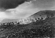 Group of Native Americans in war dress riding over hills in staged re-enactment, 1913. Photograph by by Joseph Kossuth Dixon