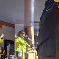 """081414  Adron Gardner<br /> <br /> Joan Gilmore motions to the newly returned uniform of her father U.S. Marine Corps Code Talker George Harlan Kirk during Code Talker Day at the Navajo Nation Museum in Window Rock Thursday. Military historian Craig Gottlieb donated the uniform to the museum.  """"We knew it had to be brought home,"""" Navajo Nation President Ben Shelly said."""
