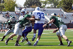 17 September 2011: Evan Hackbarth tries to hold back P.J. Cummings for runner Steve Rivera as Cameron McGlynn appears from the back side during an NCAA Division 3 football game between the Aurora Spartans and the Illinois Wesleyan Titans on Wilder Field inside Tucci Stadium in.Bloomington Illinois.