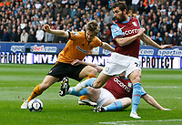 Photo: Steve Bond/Richard Lane Photography. Wolverhampton Wanderers v Aston Villa. Barclays Premiership 2009/10. 24/10/2009. Kevin Doyle (L) is tackled by Richard Dunne (obscured) as Carlos Cuellar comes in to cover