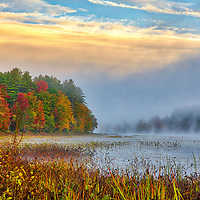 New England fall foliage and solitude on a foggy morning at Hopkinton Lake in Hopkinton, New Hampshire. <br />