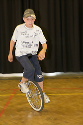 Young boy riding unicycle in school sports hall,