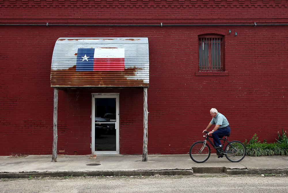 Jimmy Abel rides his bicycle past the entrance to a dance hall in downtown Crawford Thursday May 1, 2008.