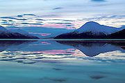 Alaska,  Gorgeous winter scenery of the Chugach Mountains reflected in the ocean waters of Turnagain Arm.   Sunset comes early around 3;00 pm.  in winter,
