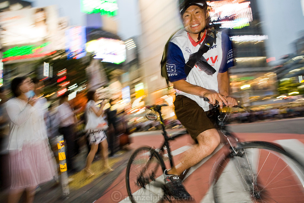 Jun Yajima, a bike Messenger, rides through a busy intersection in the Shibuya Ward (district) of Tokyo, Japan. (Jun Yajima is featured in the book, What I Eat: Around the World in 80 Diets.) MODEL RELEASED.