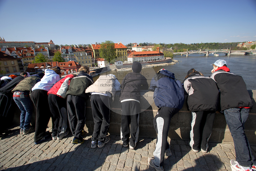 A group of sightseeing students view the landmark city scape from the Charles River Bridge in Prague, Czech Republic in the European Union on a beautiful spring day.  The Charles Bridge is a favoite of tourists on vacation the in picturesque old town.