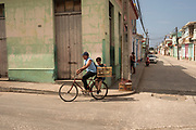 A couple crosses the city of Trinidad by bicycle carrying a cage with a bird, Cuba.