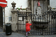 A young girl holds railings at the site of Brussels' famous landdmark, the Mannekin Pis statuette, dressed in red...Manneken Pis (literally little man pee in Marols, a dialect spoken in Brussels, also known in French as le Petit Julien), is a famous Brussels landmark. It is a small bronze fountain sculpture depicting a naked little boy urinating into the fountain's basin. It was designed by Jerome Duquesnoy and put in place in 1618 or 1619.[1] It bears a similar cultural significance as Copenhagen's Little Mermaid. The statue is dressed in costume several times each week, according to a published schedule which is posted on the railings around the fountain. His wardrobe consists of several hundred different costumes,