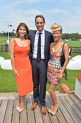 Left to right, GEMMA ARTERTON, ANDRE KONSBRUCK Director of Audi UK and THANDIE NEWTON at the Audi International Polo at Guards Polo Club, Windsor Great Park, Egham, Surrey on 26th July 2014.