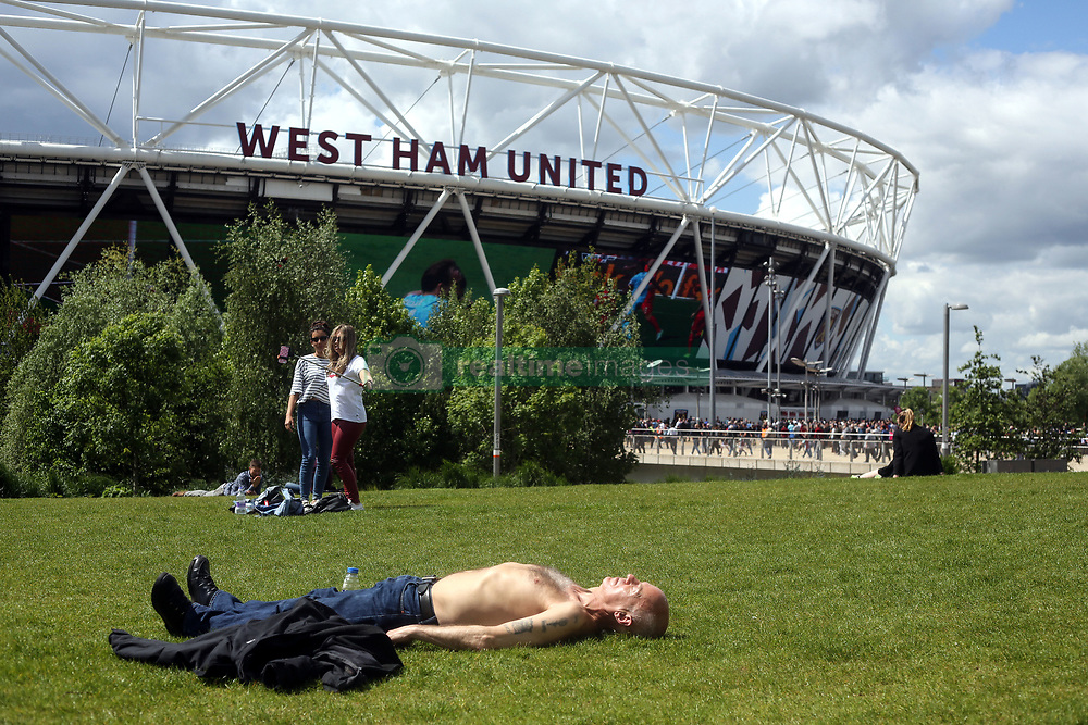 14 May 2017 - Premier League Football - West Ham United v Liverpool - A man sunbathes topless in front of The London Stadium - Photo: Charlotte Wilson