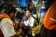"""30 NOVEMBER 2012 - BANGKOK, THAILAND:  Volunteer medics with the Ruamkatanyu Foundation treat a man injured in a motorcycle accident during a Friday night shift. The Ruamkatanyu Foundation was started more than 60 years ago as a charitable organisation that collected the dead and transported them to the nearest facility. Crews sometimes found that the person they had been called to collect wasn't dead, and they were called upon to provide emergency medical care. That's how the foundation medical and rescue service was started. The foundation has 7,000 volunteers nationwide and along with the larger Poh Teck Tung Foundation, is one of the two largest rescue services in the country. The volunteer crews were once dubbed Bangkok's """"Body Snatchers"""" but they do much more than that now.   PHOTO BY JACK KURTZ"""
