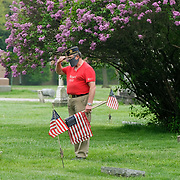 Craig Gauger, an Air Force veteran who is part of the American Legion Post 28 and Veterans of Foreign Wars Post 6170, salutes after placing a flag at a veteran's grave at Fort Meigs Cemetery in Perrysburg, Ohio, on Saturday, May 16, 2020. THE BLADE/KURT STEISS