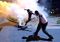 September 20, 2016 - Charlotte, North Carolina, U.S.- A protestor kicks a tear gas canister fired by Charlotte-Mecklenburg police officers along Old Concord Rd. on Tuesday night. The protest began on Old Concord Road at Bonnie Lane, where a Charlotte-Mecklenburg police officer fatally shot a man in the parking lot of The Village at College Downs apartment complex Tuesday afternoon. The man who died was identified late Tuesday as Keith Scott, 43, and the officer who fired the fatal shot was CMPD Officer Brentley Vinson. (Credit Image: © Jeff Siner/TNS via ZUMA Wire)