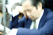 business commuter napping on a train Tokyo Japan