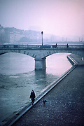 A woman with long hair walks her dog by herself along the bank of the river Seine in paris past the Archeveche bridge, 10th May 1980, Paris, France.