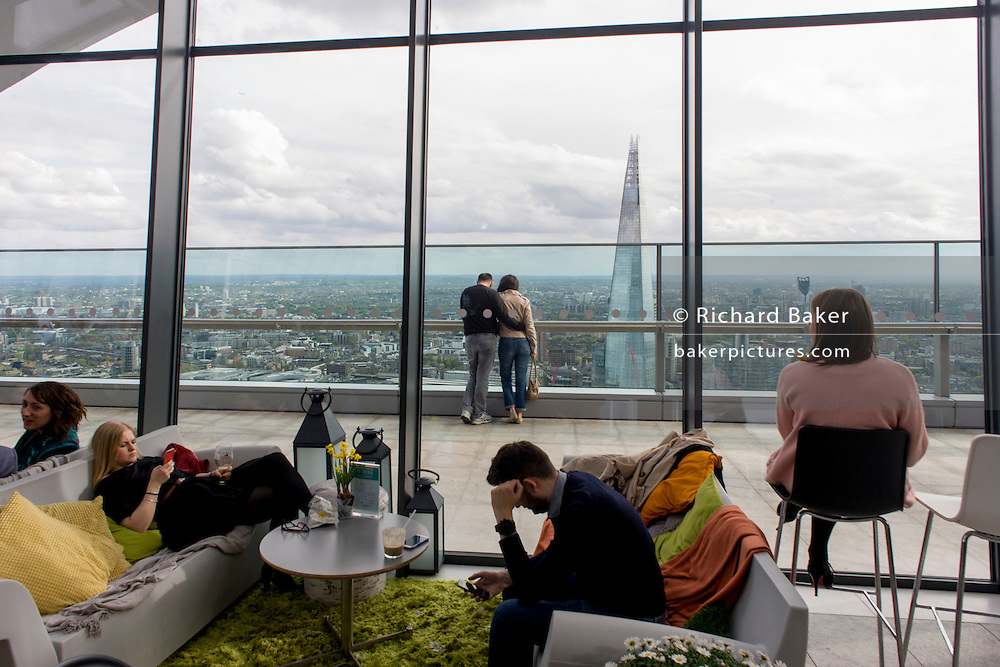 Visitors admire London skyline seen from the Sky Garden on the top of the Walkie Talkie building in the City of London.