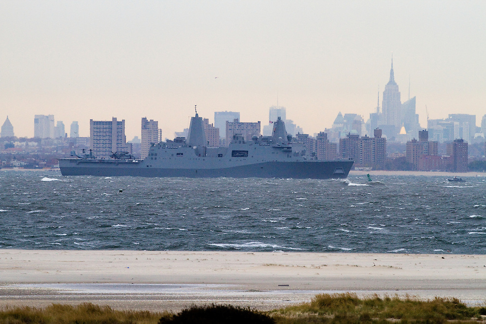 The USS New York built with steal salvaged from the World Trade Center Towers and after having been commissioned in a ceremony on November 8th in New York City leaves New York Harbor.   Behind the ship is New York City with the Empire State building standing prominently in the skyline.