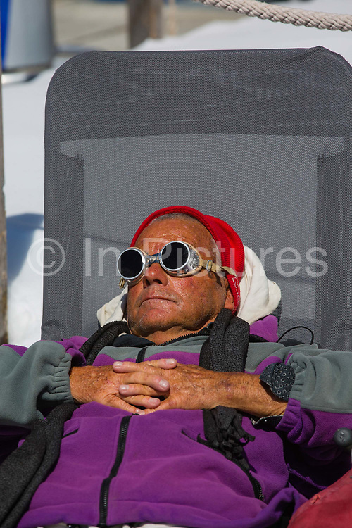 An elderly man sunbathing wearing old fashioned metal rimmed goggles on 05th May 2017 in Corvatsch, Switzerland. Piz Corvatsch is a mountain in the Bernina Range of the Alps, overlooking Lake Sils and Lake Silvaplana in the Engadin region of the canton of Graubünden.