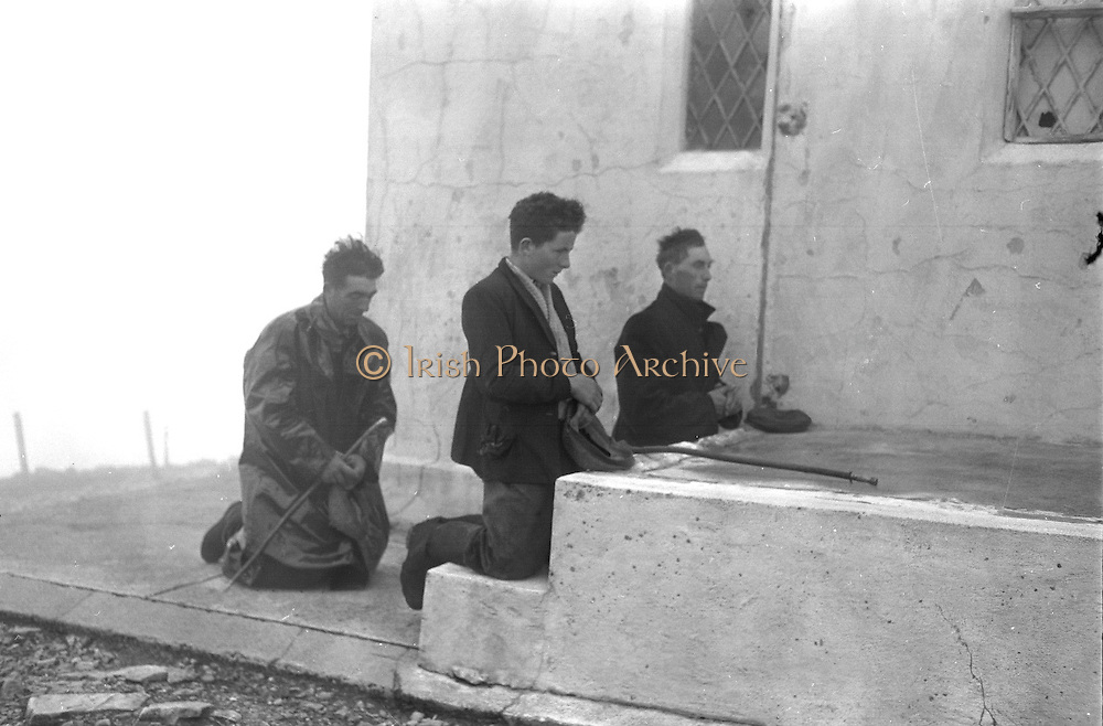 Farmers use donkeys to transport sand and cement up Croagh Patrick for work on the exterior of the Oratory. Michael McNeill, his ten year old son Michael and Patrick Walsh say a prayer on the mountain top before the descent..15-17.05.1962
