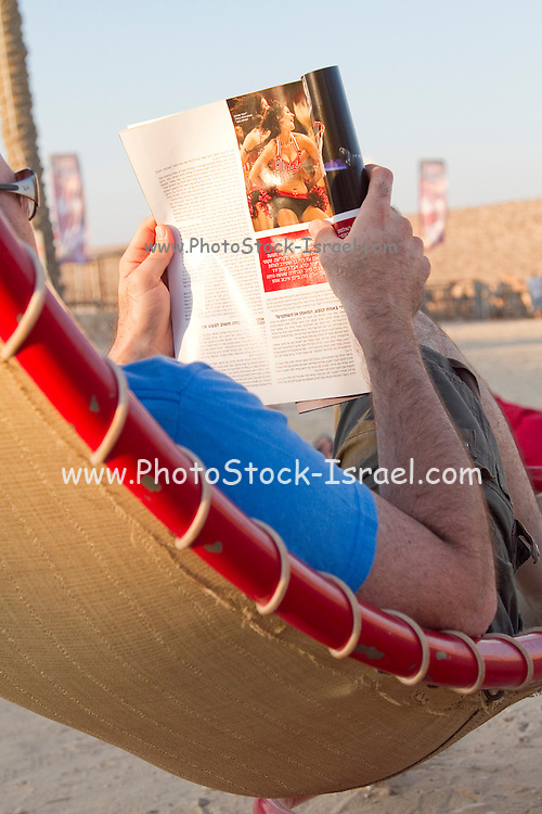Man on the beach relaxes on a hammock reads a magazine