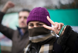 © Licensed to London News Pictures. 02/12/2011. An Iranian woman wearing a 'Democracy 4 Iran' wrist band' with demonstrators  in front of the Iranian Embassy in London Today (02/12/2011). Diplomats working at the Iranian embassy in London have been given this afternoon as a deadline to leave the UK, after the British embassy in Tehran was stormed. Photo credit: Ben Cawthra/LNP