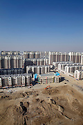 An aerial view of a new city, constructed in the outskirts of Linhe, Inner Mongolia. Every year roughly 13 million newly urbanized Chinese need homes.