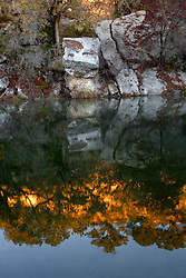 Stock photo of a reflection of boulders and trees in the river in the Texas Hill Country