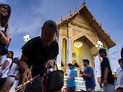 """13 MAY 2013 - BANGKOK, THAILAND: A woman makes merit for Vesak while others walks clockwise around Wat That Thong in Bangkok. Vesak, called Wisakha Bucha in Thailand, is one of the most important Buddhist holy days celebrated in Thailand. Sometimes called """"Buddha's Birthday"""", it actually marks the birth, enlightenment (nirvana), and death (Parinirvana) of Gautama Buddha in the Theravada or southern tradition. It is also celebrated in Cambodia, Laos, Myanmar, Sri Lanka and other countries where Theravada Buddhism is the dominant form of Buddhism.     PHOTO BY JACK KURTZ"""