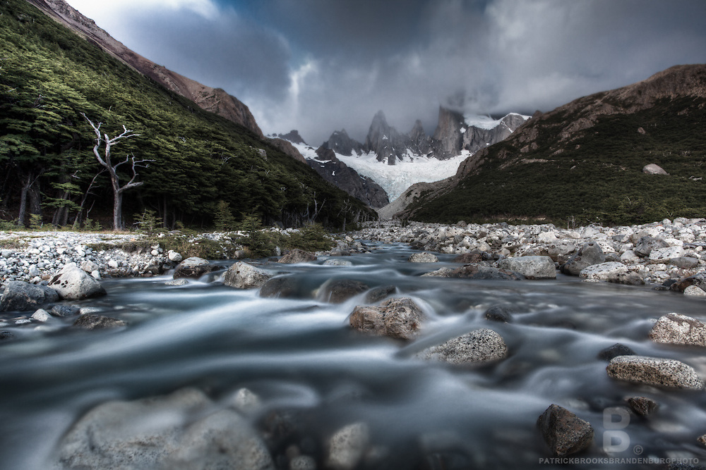 A mountainous landscape where the smooth blue waters of the river compliment the clouds, peaks trees and rocks surrounding Montt Fitz Roy in Patagonia, Argentina.
