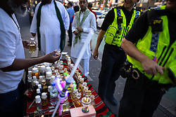 © Licensed to London News Pictures. 20/07/2021. Manchester, UK. A perfume seller offers a sample to two passing police officers . Muslims celebrate Eid al-Adha in Rusholme in Manchester. The festival marks the Islamic tale of the prophet Ibrahim , who offered his son as a sacrifice to Allah . Photo credit: Joel Goodman/LNP