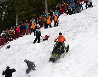 Hill helpers dive out of the way of Eban Abshire as he eyes the top of the course Saturday in his Open Mod qualifying run during the 41st annual World Championship Snowmobile Hill Climb.