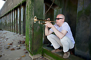 Man plays a trumpet underneath Blackfriars Bridge on the shore of the river Thames. The Mayor's Thames Festival is London's largest outdoor arts festival and one of the most spectacular events of the year. It is a celebration of London and the River Thames, one that is free and open to all. A vibrant mixture of live music, dance, art installations, carnival, river races and street arts, the festival transforms the Thames and its banks and brings Londoners together at the heart of their city.