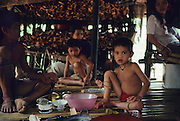 1989: Semi-nomadic Penan natives, Baru and his family, sit in a temporary 'sulap' structure having traditional food, including sago which is eaten as a paste, using bamboo forks. Long Tedang, Limbang district, Sarawak, Borneo<br /> <br /> Tropical rainforest and one of the world's richest, oldest eco-systems, flora and fauna, under threat from development, logging and deforestation. Home to indigenous Dayak native tribal peoples, farming by slash and burn cultivation, fishing and hunting wild boar. Home to the Penan, traditional nomadic hunter-gatherers, of whom only one thousand survive, eating roots, and hunting wild animals with blowpipes. Animists, Christians, they still practice traditional medicine from herbs and plants. Native people have mounted protests and blockades against logging concessions, many have been arrested and imprisoned.